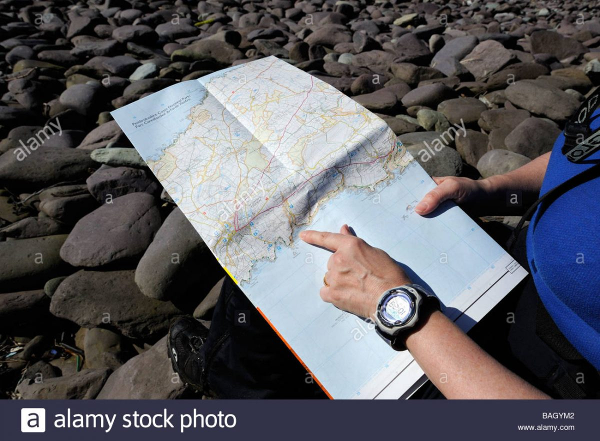 female-walker-reading-a-map-on-the-pembrokeshire-coast-path-wales-BAGYM2
